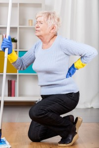 Elderly woman having back pain while cleaning